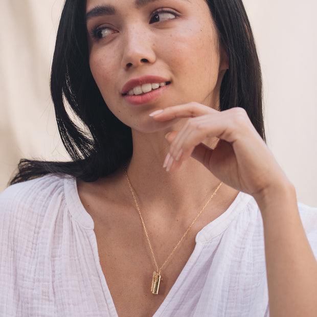 Gold Capsule necklace worn by a model.
