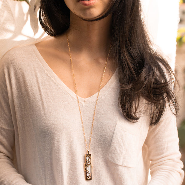 Shown here: a model wearing the cascading circles fortune locket.
