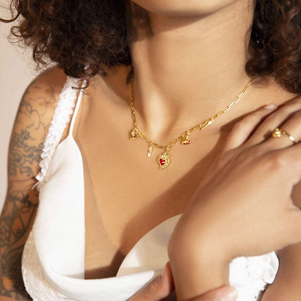Model wearing our gold heart charm necklace, with 5 heart charms that take you through the phases of love.