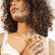 Photo of heart charm necklace on model with her hands crossed on her chest.