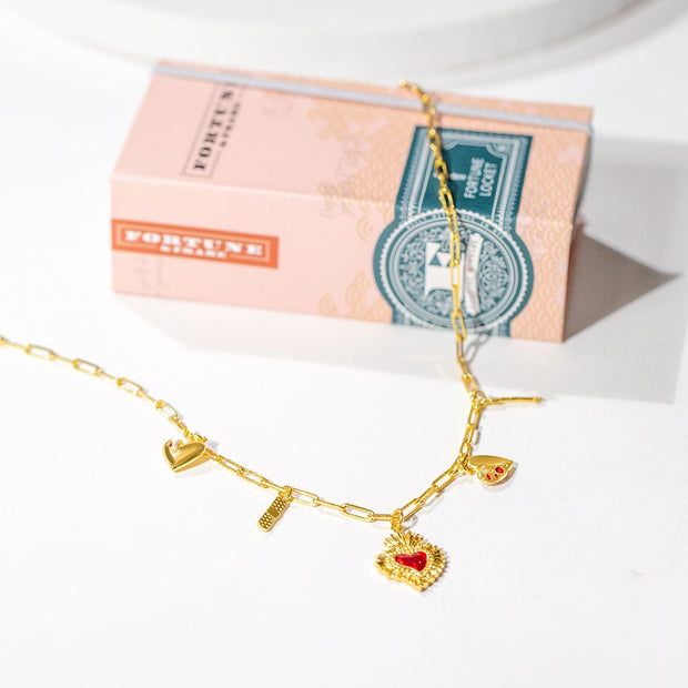Our heart charm necklace, shown strewn over our peach gift box.