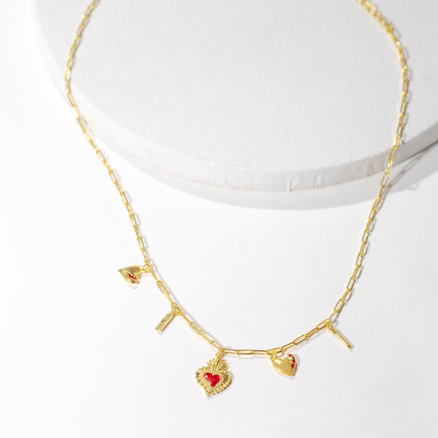 Our Heart Charm necklace: a dainty paperclip chain adorned a dainty paperclip chain with five ruby and crystal enamel-embellished charms: a broken heart, bandaid, sacred heart, jeweled heart and arrow charm.