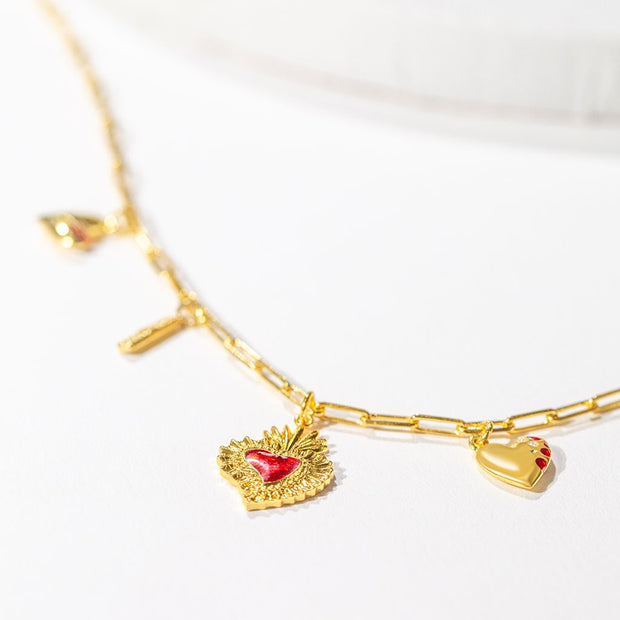 A closeup of our gold heart phases charm necklace, with a focus on the sacred heart charm pendant.
