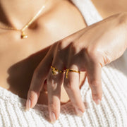 Shown here: Woman's hand wearing a mending heart charm ring and bandaid ring.