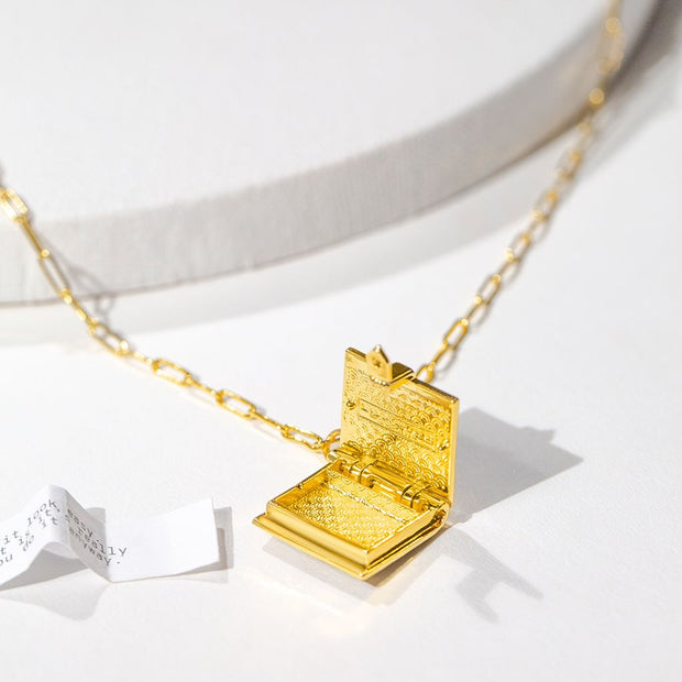Shown here: an open book locket necklace with its fortune next to it.