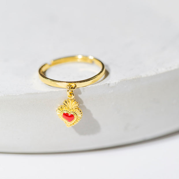 Our sacred heart charm ring is a small ruby red enamel-embellished gold heart charm dangling from a thin gold ring band. Shown here facing outward, and sitting on a round, light grey stone.