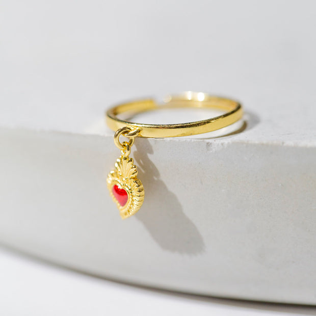 Our sacred heart charm ring is a small ruby red enamel-embellished gold heart charm dangling from a thin gold ring band. Shown here laying flat on a round, light grey stone.