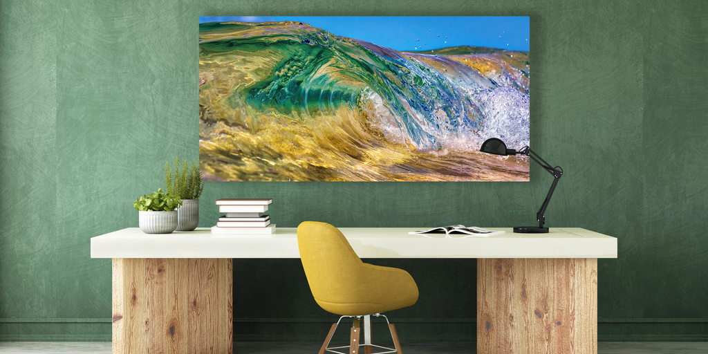 Photography artwork shows golden sand, green island and blue sky through a crystal clear wave.