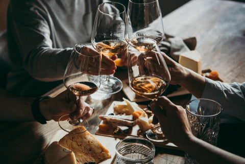 people clinking wine glasses in a toast during meal