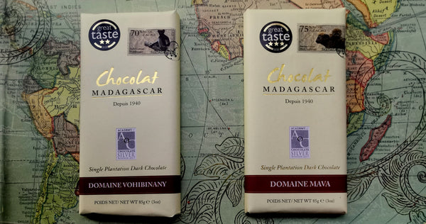 A bar of the Chocolat Madagascar single plantation Domaine MAVA dark 75% cocoa and single plantation Domaine VOHIBINANY dark 70% cocoa placed side by side on a coloured world map background with a decorative swirl pattern.