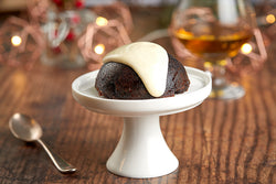 A small Christmas pudding with brandy sauce poured on top, placed on a white ceramic cake stand. Copper geometric fairy lights are placed in the background.