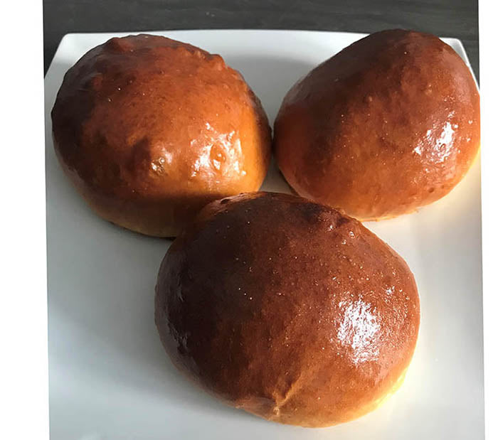 Three freshly baked brioche buns placed on a square white plate.
