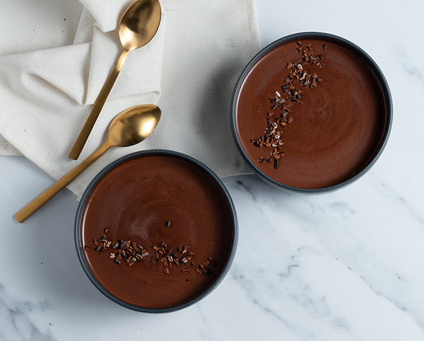 Two bowls filled with creamy chocolate mousse topped with cocoa nibs. Two golden spoons lay beside the bowls.