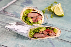 Pieces of succulent cocoa coated steak, with lettuce and smashed avocado wrapped in a floury tortilla.