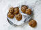 Seven pumpkin chocolate chip cookies on a tray covered with a white cloth