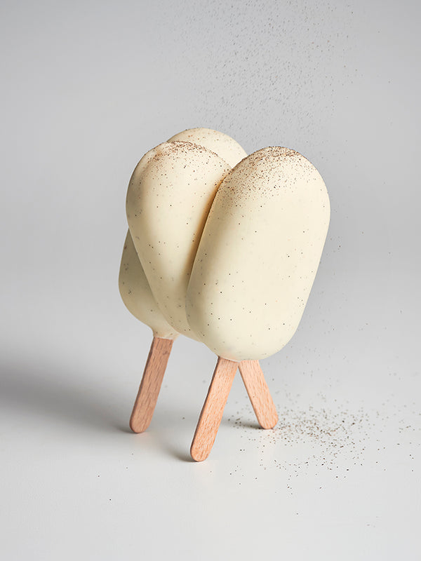 Three crunchy hazelnut & vanilla popsicles standing up on their sticks
