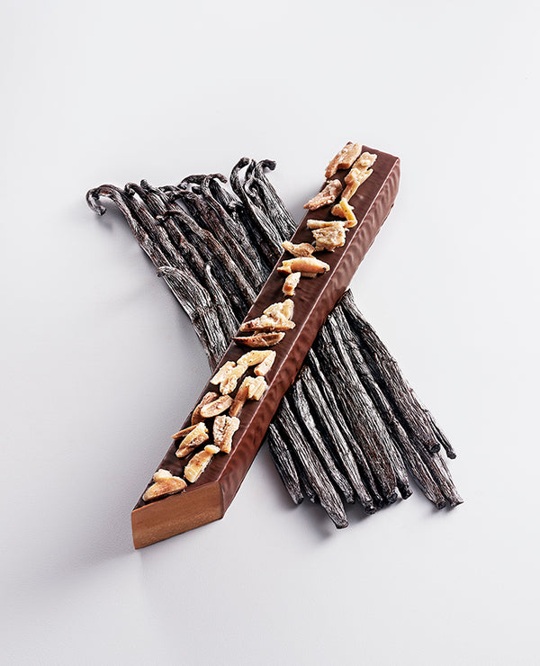 A valencian almond praliné & vanilla snack bar laying diagonally across Norohy vanilla pods