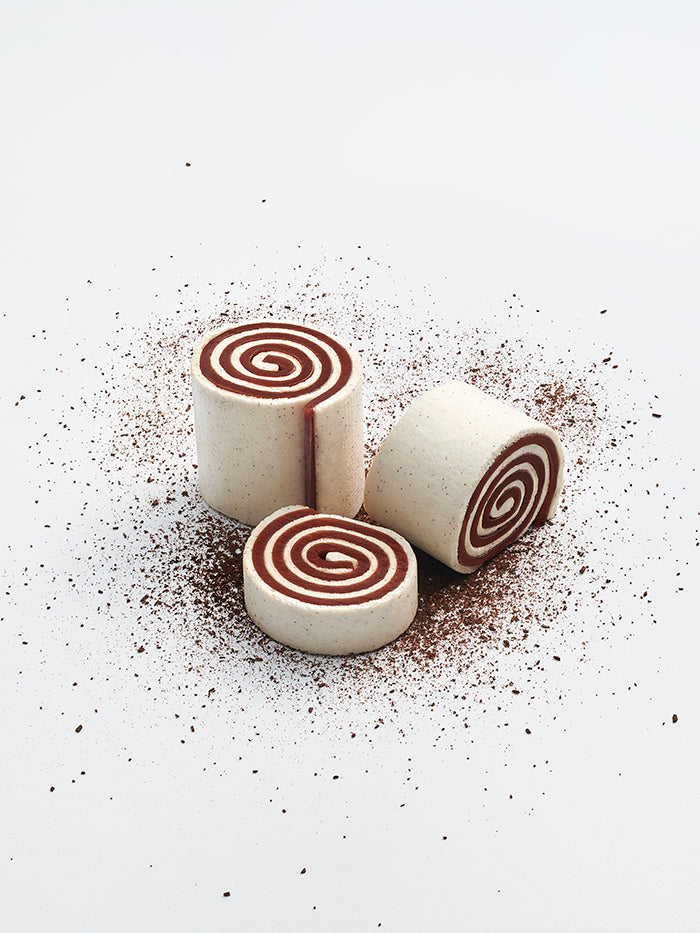 Three vanilla marshmallow and hazelnut gianduja spirals cut into different sizes, one laying on its side and two standing up.