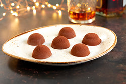 Cocoa dusted ice cream truffles placed on a white speckled plate. A glass of brandy sits next to it. With fairy lights in the background.