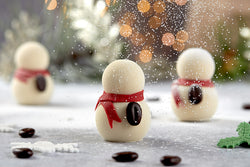 A snowman made from coffee flavoured gelato sprayed with white chocolate and decorated with a coffee bean and sugarpaste scarf