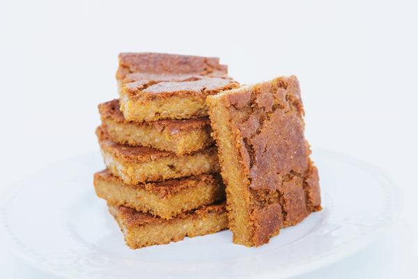 Five blondie squares stacked on top of each other on a white plate. With a single blondie leaning against the stack.