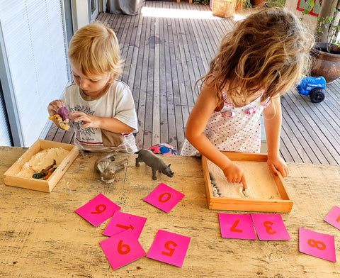 Children using Montessori sand trays for learning to write
