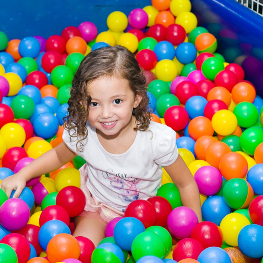 A girl playing in a ball pit filled with the FitC™ 100pc Plastic Ball Pit Balls Pack for Baby/Kids Ball Pool.