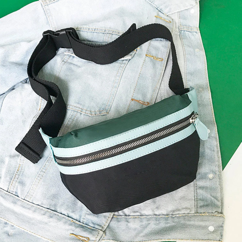 The SyWear™ Women Small Canvas Waist Crossbody Phone Black & Green Bag displayed on a jeans jacket