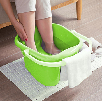 Women feet soaked in the ZenC™ Home Foot Massage Spa Massager Feet & Calm Soak Bath with a white towel on a buckets handle and a white rectangular carpet underneath.