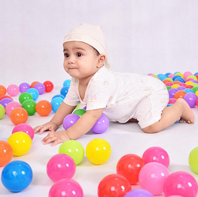 Baby playing with plastic ball as used in the FitC™ Foldable Indoor/Outdoor Baby Ball Pit Playpen for Kids w/t Ball Hop.