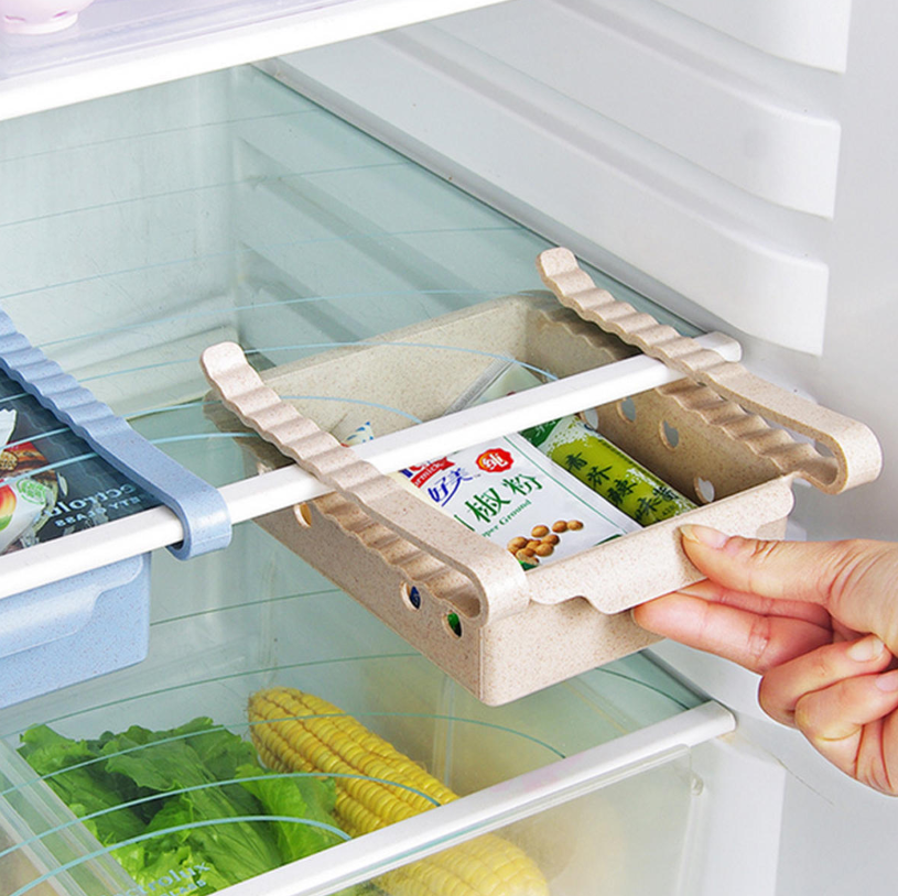 A woman's hand holding for the ServeMe™ Refrigerator Storage Organization Box Fridge Container Rack Organizer's handle and sliding it back into the fridge.