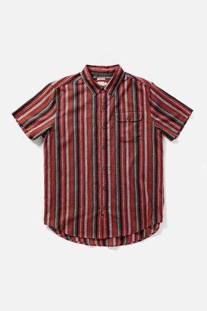 Flat lay of short sleeve button up shirt. The main color is burgundy, with white, green, and yellow in an all over stripe pattern. Single chest pocket and rounded hem.