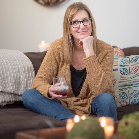Gretchen (Christina) Maser sits on a couch with a glass of her Good Food Award Winner Red Raspberry Shrub. Christina Maser Co. is a woman-owned and operated small business in Lancaster, PA.