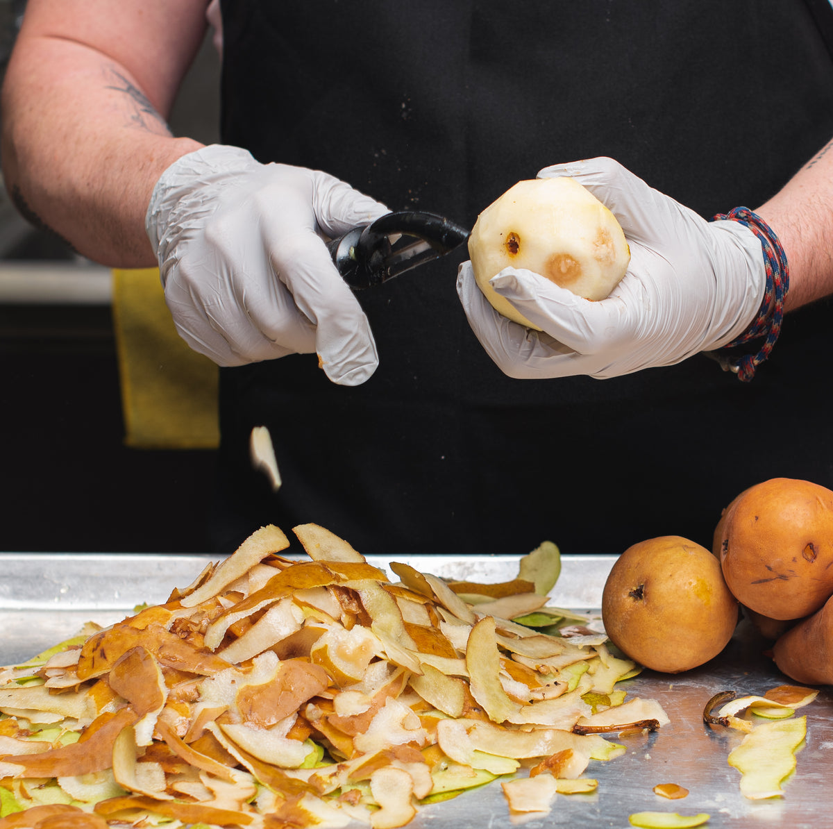 Glove hands use a vegetable peeler to remove skin from pears to be used in jams, vinaigrettes, and vinegars.