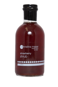 Strawberry Shrub or drinking vinegar in a wide glass bottle with a clear and white label. Made with organic sugar, apple cider vinegar, and local strawberries.
