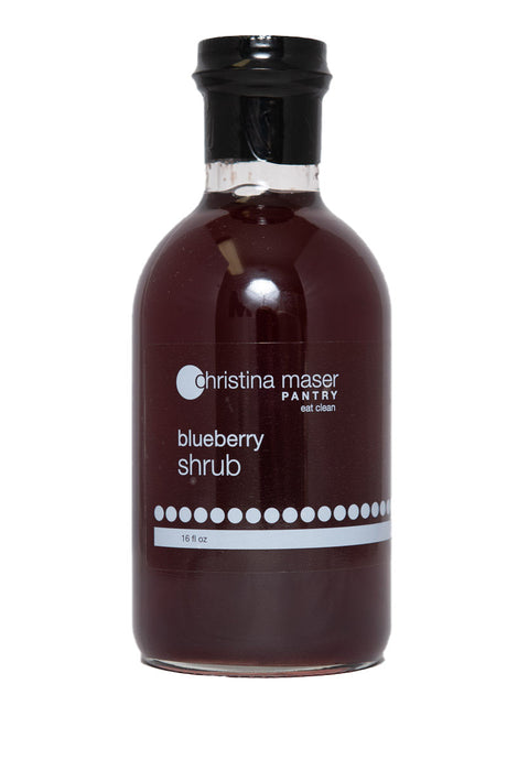 Blueberry Shrub or drinking vinegar in a wide glass bottle with a clear and white label. Made with organic sugar, apple cider vinegar, and local blueberries.