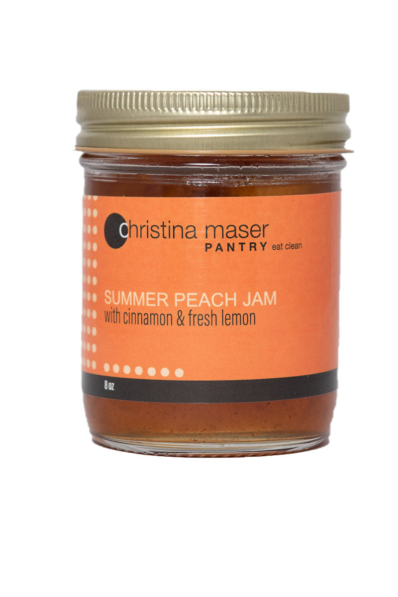 Summer peach jam in clear glass mason jar with orange label and gold metal lid.