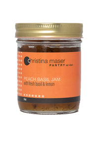 Peach Basil Jam in clear glass mason jar with orange wraparound label. Jam is made with local Lancaster County peaches and organic cane sugar.