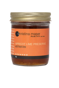 Photo of Apricot Lime Preserve organic jam in a glass mason jar with orange wraparound label.
