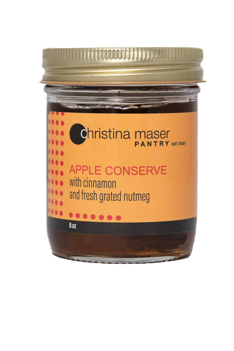 Photo of Apple Conserve organic jam in a glass mason jar with orange wrap label.