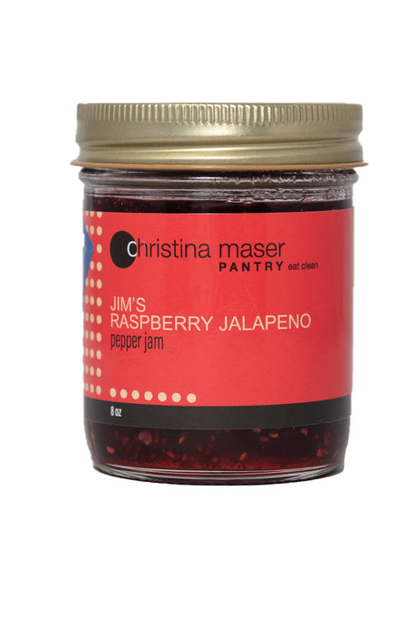 Good Food Award winning Raspberry Jalapeno Pepper Jam in clear glass jar with red wraparound label. Made with local peppers and organic cane sugar.