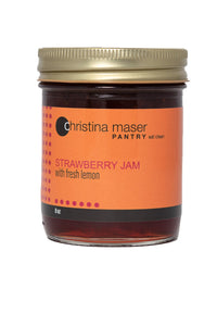 Classic strawberry jam in clear glass mason jar with orange label and gold metal lid.