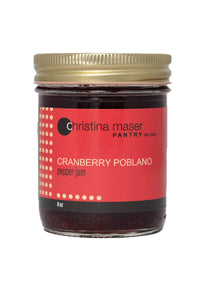 Cranberry Poblano Pepper jam. Full of sweet heat. A clear glass jar with a red wraparound label with beige accents.