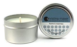 thyme & rosemary soy wax candle in silver metal tin with lid featuring teal label.