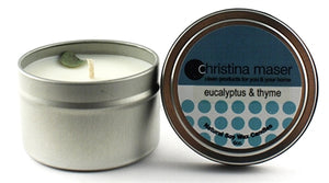 Eucalyptus and Thyme soy wax candle in silver metal tin. Candle has a dried eucalyptus leaf as a topper. Lid features a teal label.