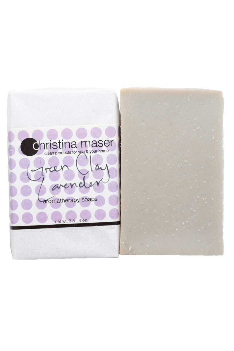 Green Clay lavender vegan bar soap. Handmade soap is slate grey. Bar is wrapped in white paper with lavender colored dot accents on the label.