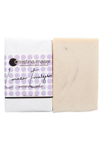 Lavender Eucalyptus vegan bar soap. Soap is natural colored. Bar is wrapped in white paper with a label with purple dot accents and black text.