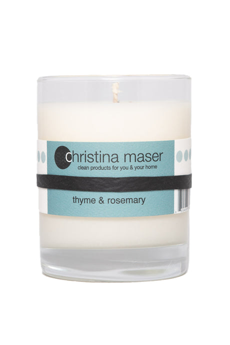 thyme and rosemary soy wax candle in clear glass tumbler with teal label.
