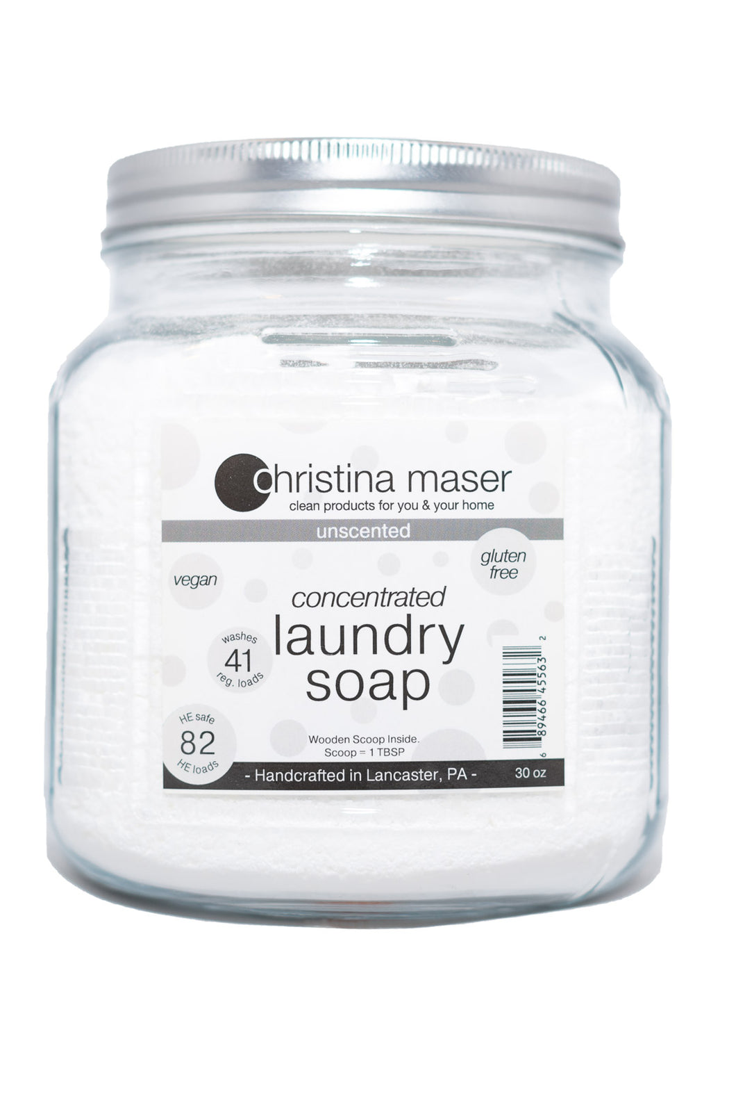 Powdered concentrated vegan laundry soap in a large glass jar. Comes with wooden scoop. Unscented and safe for baby laundry or sensitive skin. Reusable. Label is white with grey accents.
