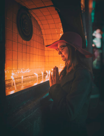 Woman praying in front of candles